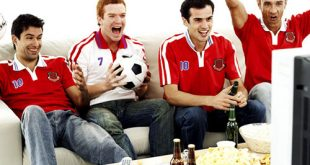 Group of Football Fans Sitting on a Couch and Watching the Game --- Image by © Royalty-Free/Corbis